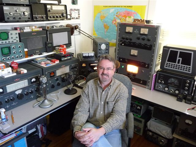 Clark sitting in between two tables of vintage equipment. Globe King, Hallicrafters, Drake and Heathkit equipment