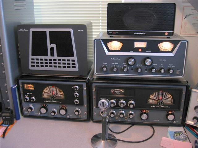 Old Hallicrafters station with HT32 transmitter and SX-115 receiver and transmitter and an additional older model receiver. Speaker with bit H sitting on top of the receiver and sitting on top of the HT32.  I see a SX-122 receiver sitting on top of the HT-32 transmitter with a Hallicrafters speaker sitting on top of that.