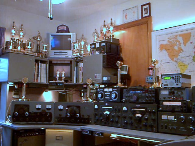 Ralph shows us a vintage AM station consisting of a Johnson Viking 500, Johnson Viking Valiant,  and a couple of Collins 75A4 receivers. Sitting on a couple shelves above are maybe a dozen old transmitting tubes in sockets with the filaments lit up giveing the room a nice glow.
