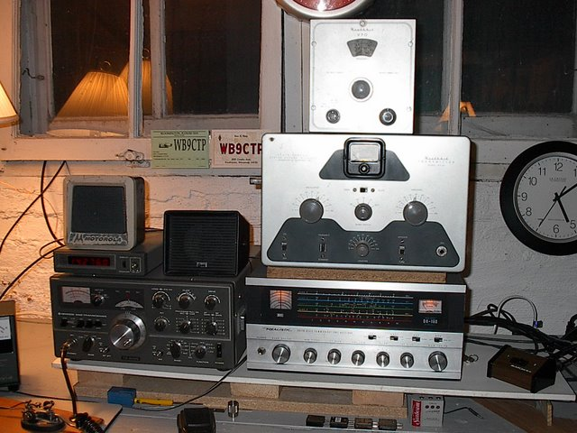 Down in Ron's basement we have a Kenwood TS-520S. Sitting on top of the Kenwood is a Moitorola Motrac speaker, and digital display. To the right of the Kenwood is the vintage AM stack consisting of (from top to bottom) Heathkit VF-1 VFO, DX-20, and Realistic DX-160 receiver. On the operating desk is Ron's straight key for slow speed CW. All radios are sitting on a shelf above the operating desk. Under the receiver we see 4 crystals for the DX-20.