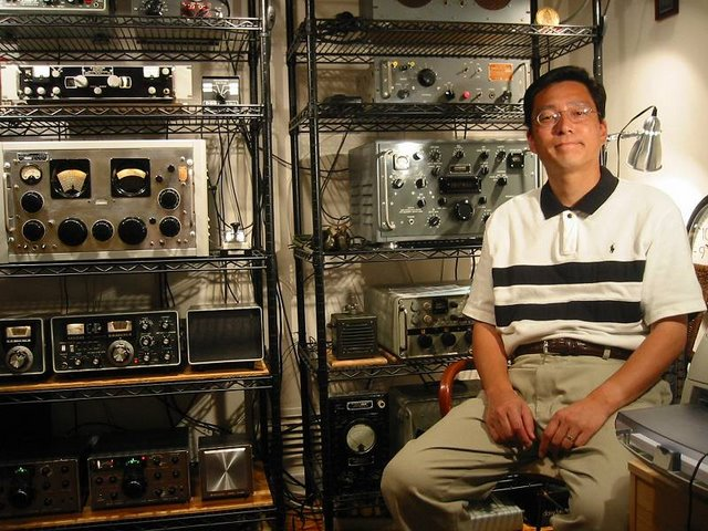 Masa sitting  next to two racks of radios. Each rack has four or five shelves loaded with cool equipment. You will have to ask Masa what it all is.