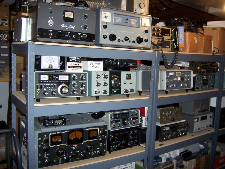Three level storage rack about three units wide containing Globe chief, Hammarlund receiver, old Yaesu transceiver, HW101, another transceiver, Hallicrafters Sky Buddy, and four or five more transceivers and I can't see what's on the lower level